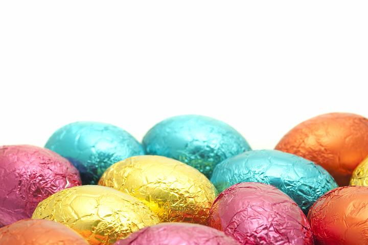 A flat arrangement of colourfully wrapped Easter Eggs with shall dof and copyspace